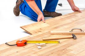 stock photo of laminate  - carpenter worker installing laminate flooring in the room - JPG