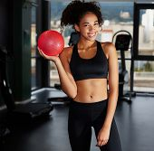 Постер, плакат: Portrait of pretty afro american girl holding pilates toning ball at gym