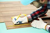 image of laminate  - Carpenter worker installing laminate flooring in the room - JPG