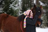 stock photo of horse girl  - Beautiful teenager girl hugging brown horse in winter forest