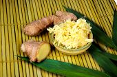 pic of ginger  - Two pieces of root ginger with a dish of grated ginger against a bamboo background - JPG