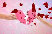 foto of broken hearted  - Hands holding two halves of broken heart against digitally generated girly heart design - JPG