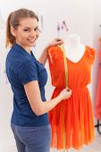 pic of dress mannequin  - Beautiful female fashion designer measuring dress on the mannequin and looking over shoulder - JPG