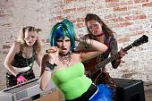 picture of groupies  - Young all girl punk rock band performs in front of brick wall - JPG