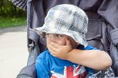 foto of scared  - scared little boy covers mouth with his hand - JPG