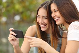 picture of socialism  - Two funny women friends laughing and sharing social media videos in a smart phone outdoors - JPG