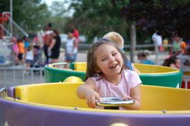 picture of amusement park rides  - Four year old girl riding on th etea cups at an amusement park - JPG
