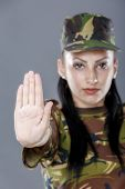 stock photo of soldier  - Soldier woman showing palm stop sign on gray background - JPG