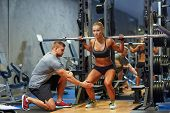 sport, fitness, teamwork, bodybuilding and people concept - young woman and personal trainer with ba poster