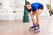stock photo of skate  - Pretty young brunette putting her inline skates on and getting ready for skating in the city - JPG
