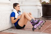picture of inline skating  - Portrait of a pretty female skater relaxing and drinking some water after skating in the city - JPG