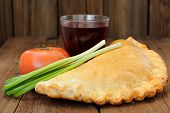 image of scallion  - Pizza calzone with glass of red wine fresh scallion and tomato closeup - JPG