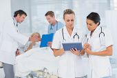 foto of clipboard  - Doctors looking at clipboard while theirs colleagues speaks with patient in the hospital - JPG