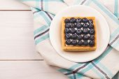 picture of custard  - Tartlet with bluebarries and custard on a white plate over a blue checkered napkin and wooden background - JPG