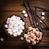image of sugar cube  - White and brown sugar cubes in bowsl and vanilla beans on dark painted wooden background - JPG