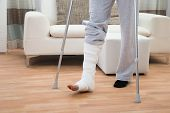 pic of crutch  - Low Section Of A Disabled Man Using Crutches For Walking - JPG
