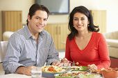 picture of hispanic  - Young Hispanic Couple Enjoying Meal At Home - JPG