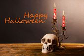 image of bloody  - Bloody candles for Halloween holiday and decorative skull on wooden table - JPG