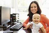picture of hispanic  - Hispanic mother with baby in working home office - JPG