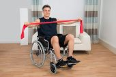 stock photo of handicap  - Handicapped Man On Wheelchair Exercising With Resistance Band At Home - JPG
