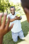 image of pistols  - African American Grandfather And Grandson Playing With Water Pistols In Park - JPG