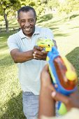 foto of pistols  - African American Grandfather And Grandson Playing With Water Pistols In Park - JPG