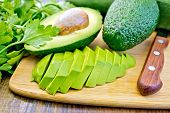 Постер, плакат: Avocado slices on board with knife