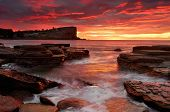 stock photo of fieri  - Fiery colours of the sunrise blanket the clouds and sky in rich flaming reds and yellows - JPG