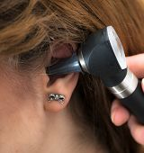 stock photo of otoscope  - woman doctor checking the patient - JPG