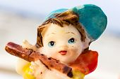 picture of flute  - macro photography depicting a small statue of a young boy playing flute - JPG