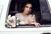 foto of luxury cars  - fashion photo of beautiful sensual bride with dark hair in luxurious lace wedding dress posing in car - JPG