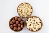 image of pine nut  - Three types of nuts in a round wooden form  - JPG