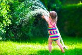 pic of sprinkler  - Child playing with garden sprinkler - JPG