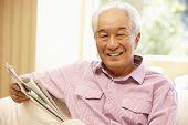 stock photo of newspaper  - Senior Asian man reading newspaper - JPG