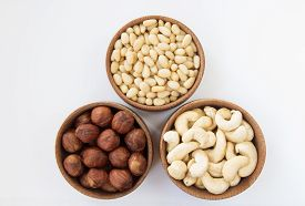 stock photo of pine nut  - Three types of nuts in a round wooden form  - JPG