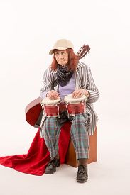 stock photo of bongo  - Funny elderly lady makes music with a wooden bongo - JPG