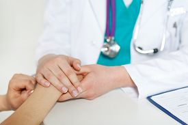 stock photo of empathy  - Beautiful female doctor holding patient - JPG
