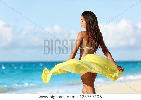 Carefree beautiful sexy bikini body woman relaxing in yellow flowing cover-up beachwear fashion wrap