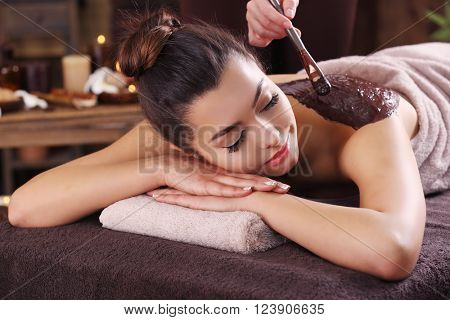 poster of Beautiful young girl having cosmetic mask in spa salon