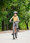 stock photo of summer fun  - Young boy riding bicycle on a summer day - JPG