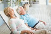 Senior couple relaxing on lounge chair at porch poster