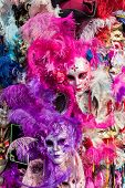 Ornated carnival masks among colorful feathers in Venice, Italy. poster
