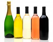 A group of five wine and champagne bottles on a white background. Bottles have no labels and reflect