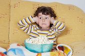 pic of televisor  - Kid watching a scary movie eating pop corn - JPG