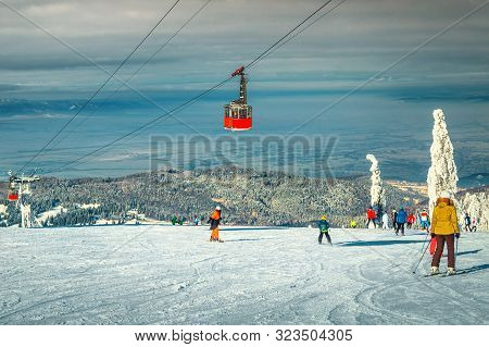 poster of Amazing Snow Covered Trees And Winter Ski Resort With Colorful Fast Cable Cars. Active Skiers Skiing