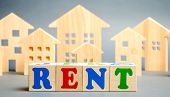 Wooden Blocks With The Word Rent And Wooden Houses. The Concept Of Renting Housing And Real Estate.  poster