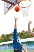 Two basketball pllayers jumping with outstretched hands to the basketball net, playing basketball poster