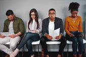 Worried And Stressed Man Holding His Resume Sitting With Other Candidates Waiting For The Job Interv poster