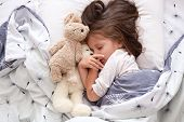 Close Up Portrait Of Toddler Girl Laying With Her Toy Teddy Bear In Bed, Posing With Closed Eyes, Ha poster