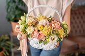 Flower Arrangement In Wicker Basket. Beautiful Bouquet Of Mixed Flowers In Woman Hand. Floral Shop C poster